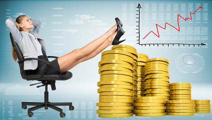 Businesswoman sitting on office chair with golden coins