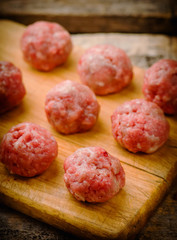 Raw meat balls on a chopping board.