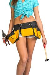 Woman wearing shirt, shorts and tool belt, holding hammer