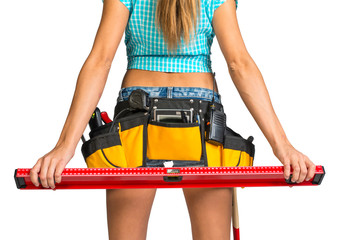 Woman wearing tool belt with tools holding builders level, close