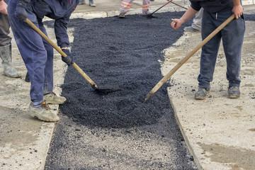 Asphalt workers with shovels patching asphalt