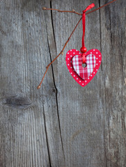 Red heart, hanging on a branch over the  wooden background.
