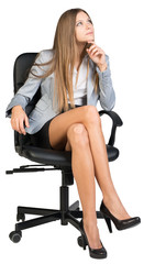 Businesswoman on office chair with her finger under chin