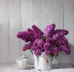 Cup of coffee and Lilac Bouquet  against a wooden board.