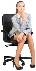 Businesswoman on office chair holding forefinger at her lower