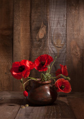 Poppies in clay pot on old wooden background.