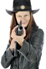 Frau als Cowboy verkleidet zielt mit Gewehr