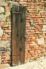 Brick wall of the old house with a wooden door