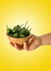 hand holding green peppers