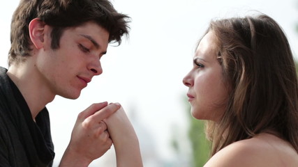 a young man holds the hand of a beautiful woman, and declares his love and kiss