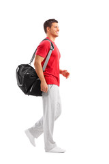 Male athlete walking with a sports bag