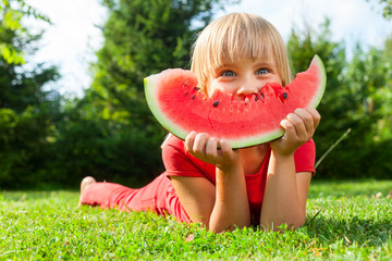 Child with slice of melon outdoor