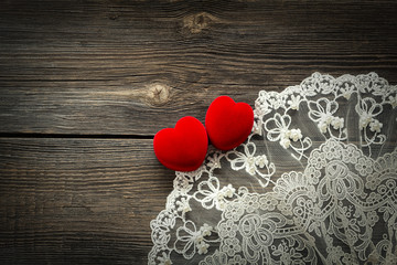Wooden background with lace and red velvet hearts
