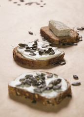 Different kinds of bred with cheese spread and pumpkin seeds