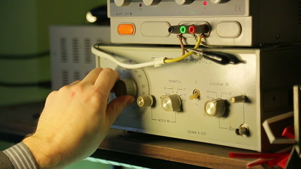 Low-frequency signal generator, a scientist controls
