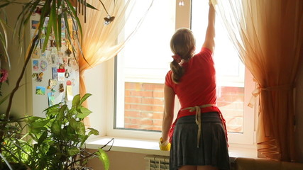 Girl washes the window in the kitchen at home, view from the bac