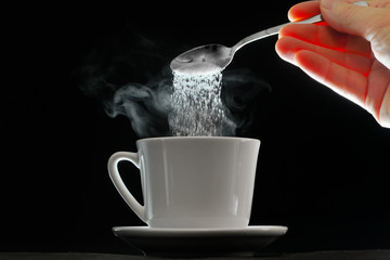 Coffee cup and pouring sugar spoon