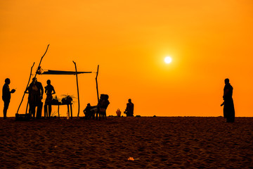 People  silhoettes at sunset on a beach