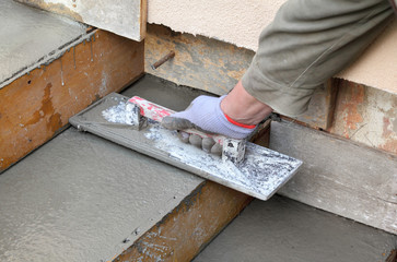 Staircase at construction site trowel, concrete, worker hand