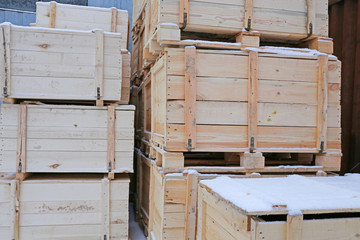 Several wooden crates covered with a small amount of snow