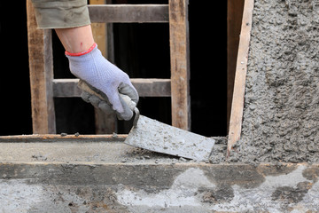 Concrete staircase making at construction site, trowel and hand