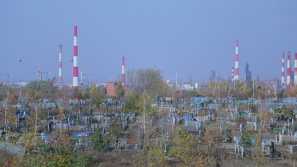 Cemetery on the background of an oil refinery, symbolic picture
