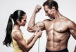 Woman measuring athletic's man biceps