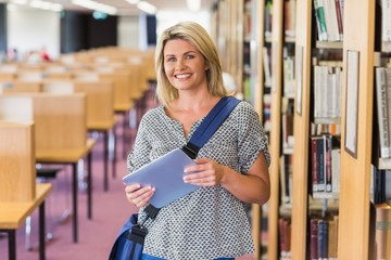 Mature student studying in the library with tablet