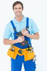 Confident carpenter holding drill machine