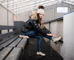 Cheerful girl putting on skates  on ice skating rink