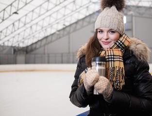 Girl with mug of hot drink on ice skating rink