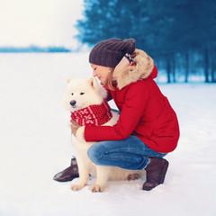 Happy woman owner embracing white Samoyed dog outdoors