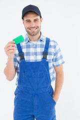 Smiling young repairman holding green card