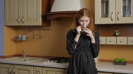 Girl drinking tea in the kitchen and dreams