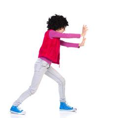 Girl pushing a wall