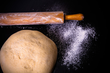 Dough, rolling pin and flour on a black background. Toned
