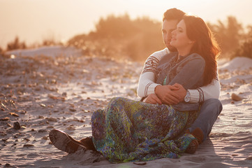 Lovely young couple on the sunset beach, selective focus