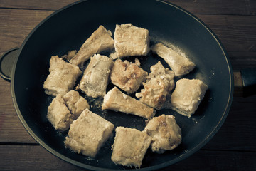 Some pieces of fried fish filet in a frying pan. Toned