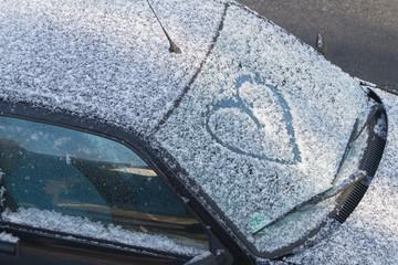 Herz auf einer zugeschneiten Windschutzscheibe