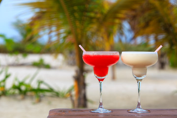 Classic and strawberry margarita cocktails on tropical beach