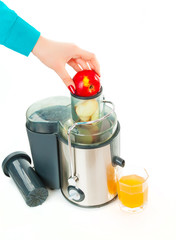 Woman hand take apple. Juice extractor and freshly squeezed appl