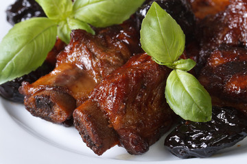 Pork ribs stewed with prunes macro. horizontal top view
