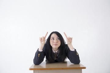 机に座る女子学生 コピースペース