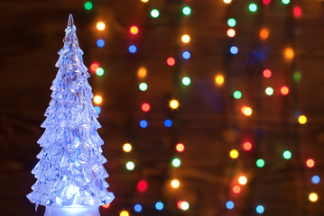 Crystal Christmas tree illuminated with a garland on the backgro