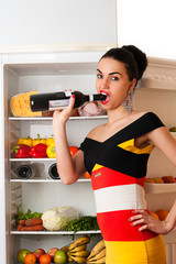 woman opens a bottle of wine teeth next to the fridge