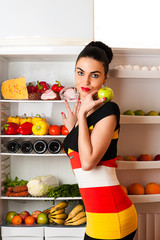 attractive woman in dress standing at the fridge