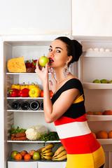 beautiful woman eating an apple in the fridge
