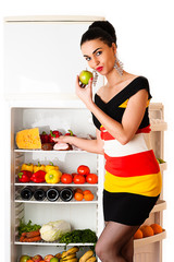 beautiful woman in dress standing at the fridge