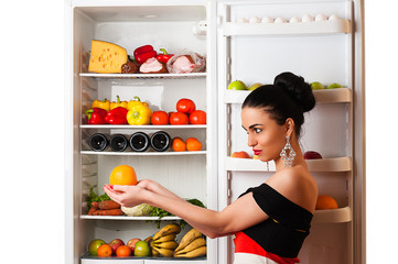 luxurious rich woman with orange in hands and fridge