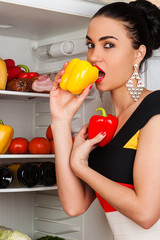 beautiful woman eats yellow peppers in the fridge